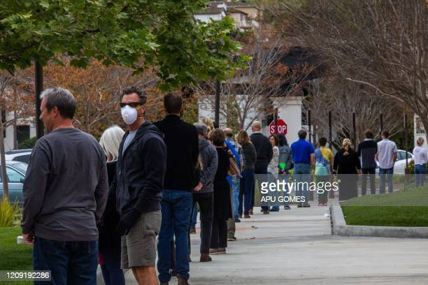 People wait in line to get into the Godspeaker Calvary Chapel sanctuary to take communion after watching Palm Sunday Service on April 5 2020 in...