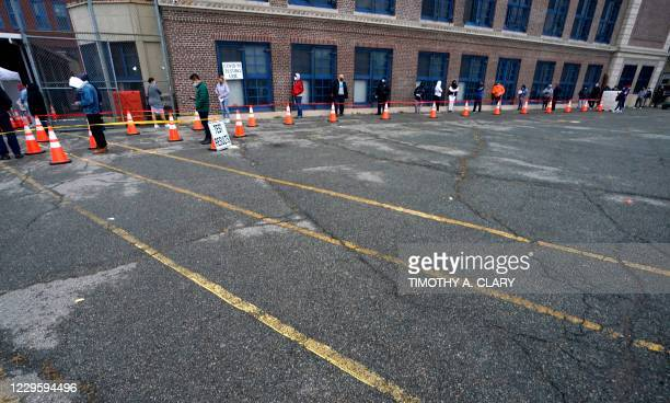 People wait in line to get tested for Covid-19 at the Ann Street School Covid-19 Testing Center in Newark, New Jersey on November 12, 2020. - US...