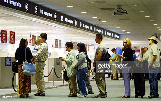 People wait in line to have their passports checked by Immigration inspectors July 2, 2002 at Miami International Airport in Miami, Forida....