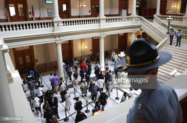 People wait in line to pay their respects at the flag-draped casket of Rep. John Lewis as he lays in repose at the Georgia State Capitol on July 29,...
