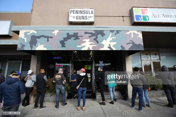 People wait in line to purchase guns and ammunition at Peninsula Guns and Tactical on March 16 2020 in San Bruno California Six San Francisco Bay...