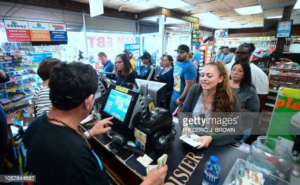 People wait in line to purchase their lottery tickets at the Blue Bird Liquor store in Hawthorne California on October 23 2018 ahead of the drawing...