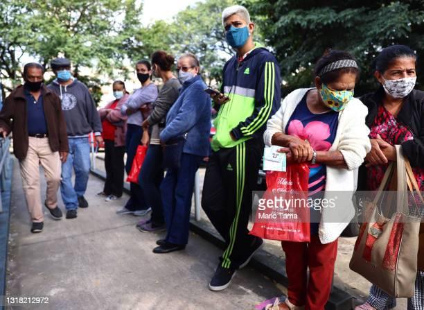 People wait in line to receive a dose of the AstraZeneca/Fiocruz COVID-19 vaccine at a public health center in the Vila Pereira Barreto neighborhood...