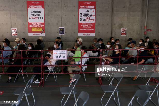 People wait in line to receive a dose of the Pfizer-BioNTech Covid-19 vaccine at a mass inoculation site at Noevir Stadium Kobe in Kobe, Japan, on...