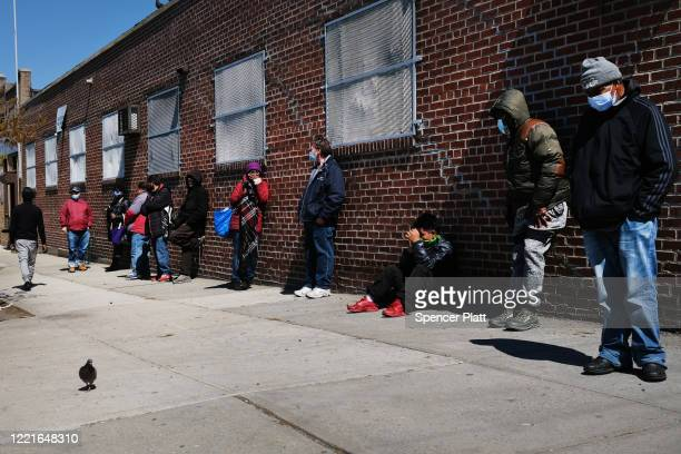 People wait in line to receive food at a food bank on April 28, 2020 in the Brooklyn borough of New York City. Food banks around the nation have...
