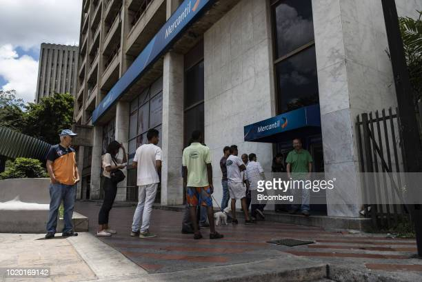 People wait in line to withdraw new sovereign bolivar banknotes at Mercantil Bank automated teller machines in Caracas Venezuela on Monday Aug 20...