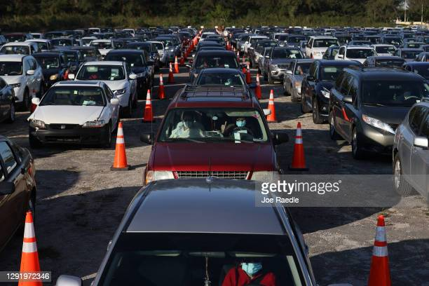 People wait in line to receive one of 5,000 grocery gift cards worth $250 each being given out by the City of Hialeah on December 18, 2020 in...