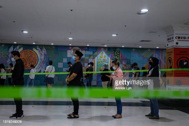 People wait in line to receive the AstraZeneca COVID-19 vaccine at a vaccination centre on May 21, 2021 in Kuala Lumpur, Malaysia. Malaysian...