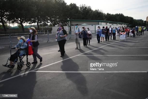 People wait in line to receive the COVID-19 vaccine at a mass vaccination site in a parking lot for Disneyland Resort on January 13, 2021 in Anaheim,...