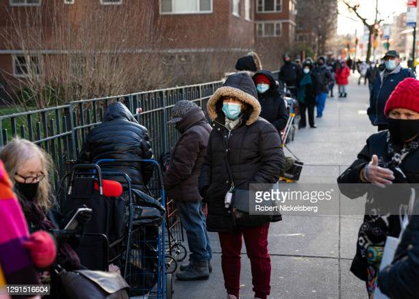 People wait in line to receive uncooked food donations from the food pantry at the Holy Apostles Soup Kitchen on December 15, 2020 in New York City....