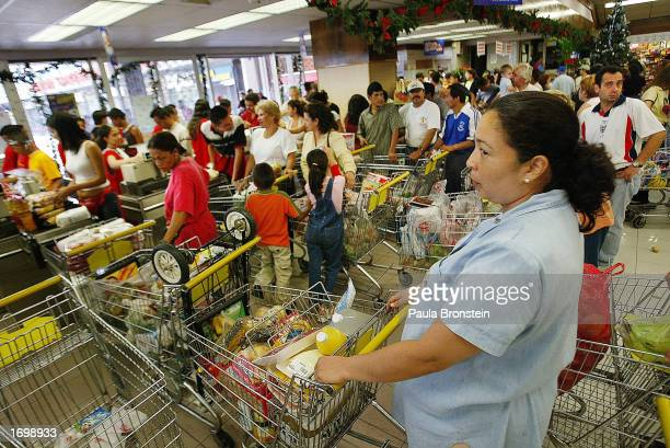 People wait in line to stock up on groceries at a crowded supermarket December 22 2002 in Caracas Venezuela The South American country is in the...