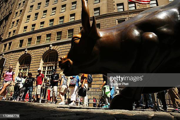 People wait in line to take a picture with the bronze bull in the Financial district which has become a Wall Street icon during afternoon trading on...