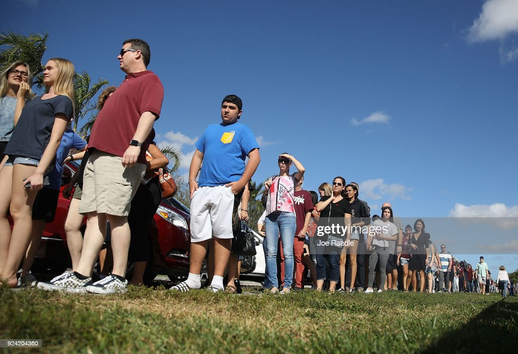 People wait in line to visit Marjory Stoneman Douglas High School on February 25, 2018 in Parkland, Florida. Today, students and parents were allowed on campus for the first time since the shooting that killed 17 people on February 14. Police arrested 19-year-old former student Nikolas Cruz for the 17 murders.