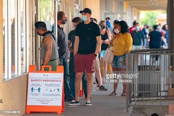 People wait in line to vote at a polling place at the Scottsdale Plaza Shopping Center, in Scottsdale, Arizona, on November 3, 2020. - The US started...