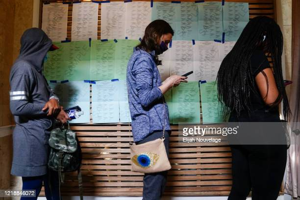People wait in line to vote in front of a wall of sample ballots for each party during Georgias Primary Election on June 9 2020 in Atlanta Georgia...