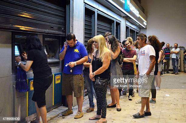 People wait in line to withdraw cash from an ATM on June 28 2015 in Athens Greece