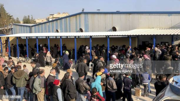 People wait in long queues in front of a bakery to buy bread as the Bashar al-Assad regime, which is incapable of meeting the basic needs of the...