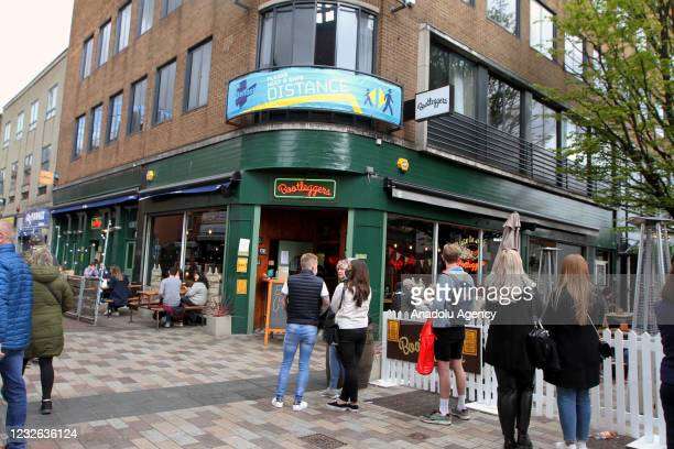 People wait in queues while keeping social distance outside a store as shops, pubs, cafes and gyms reopened their doors to customers throughout...