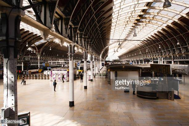 People wait in the concourse of a near-deserted Paddington Station in London, England, on March 23, 2020. Train services across the country began to...