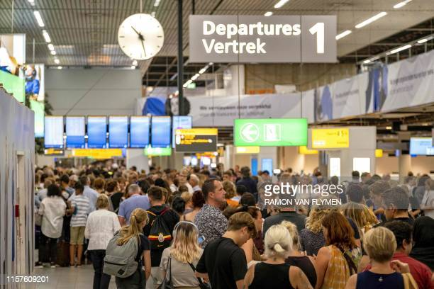 People wait in the departure hall of the AmsterdamSchiphol airport southwest of Amsterdam as a problem with refuelling grounded several dozen planes...