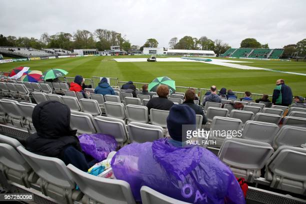 People wait in their seats as groundsmen work on the wet pitch at Malahide cricket club in Dublin as the start of play is delayed on the first day of...