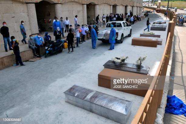 People wait next to coffins and cardboard boxes to bury their loved ones outside a cemetery in Guayaquyil, Ecuador, on April 6, 2020. - Soaring...