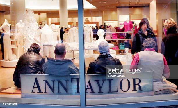 People wait on a bench near the entrance of the Ann Taylor store along the Michigan Avenue shopping district November 12 2004 in Chicago Illinois...