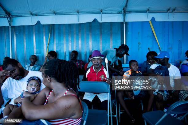 People wait on a cargo ship for evacuation to Nassau at the port after Hurricane Dorian September 7 in Marsh Harbor Great Abaco Bahamians who lost...