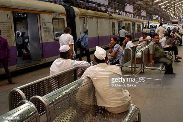 People wait on a platform at Churchgate Railway Station in Mumbai