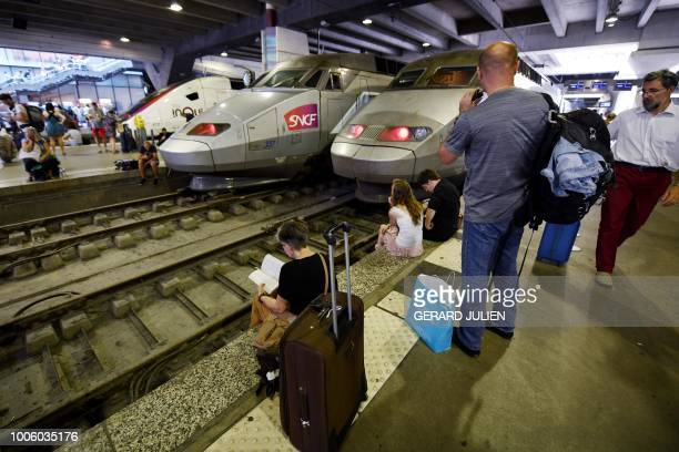 People wait on a platform of the Montparnasse railway station in Paris after several trains have been delayed following a fire of an electric...