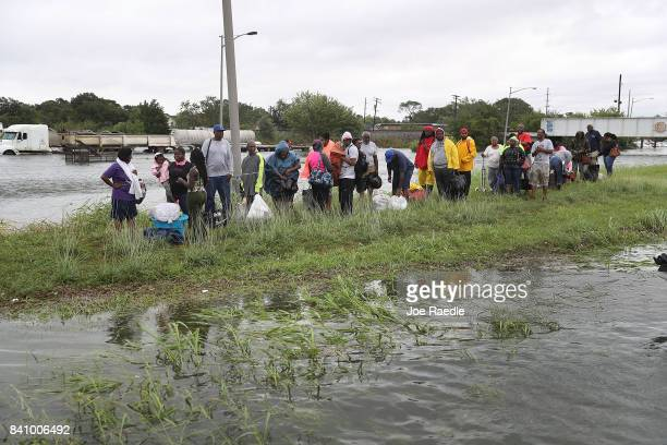 People wait on a strip of dry land for rescue boats after being driven from their homes by the flooding from Hurricane Harvey on August 30 2017 in...