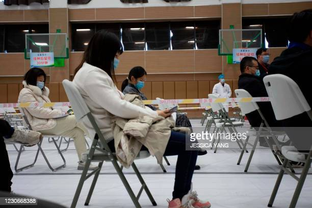 People wait on chairs after being inoculated with a Covid-19 vaccine at Jiading Stadium, a temporary vaccination site in Shanghai on January 19, 2021.