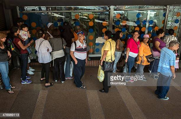 People wait on line to enter a supermarket in Caracas Venezuela on Tuesday March 4 2014 Antigovernment protests have continued in Venezuela since...