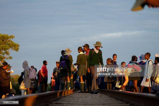 People wait on railway tracks to board a commuter train on January 29, 2019 in Cowdray Park township, in Bulawayo, Zimbabwe. - Zimbabwe's only...