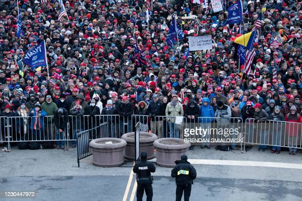 People wait on the National Mall outside a security perimeter for a rally of supporters of US President Donald Trump challenging the results of the...