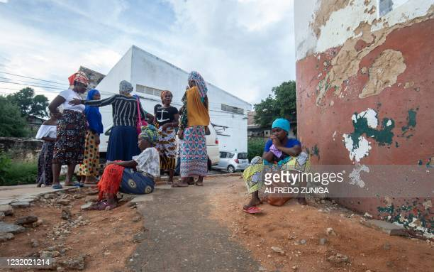 People wait on the outskirts of the seaport of Pemba on March 30, 2021 for the possible arrival of their families evacuated from the coasts of Afungi...