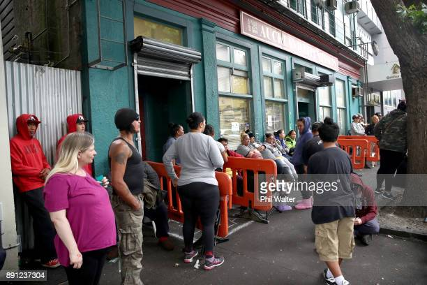 People wait on the street outside Auckland City Mission as they await donations of food and Christmas presents for their families over Christmas on...