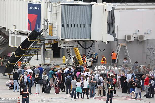 People wait on the tarmac of Fort LauderdaleHollywood International airport after a shooting took place near the baggage claim on January 6 2017 in...