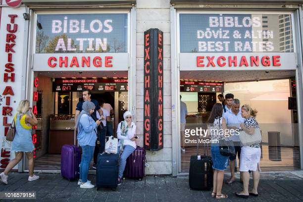 People wait outside a currency exchange office on August 14 2018 in Istanbul Turkey The Turkish Lira recovered slightly Tuesday after the previous...