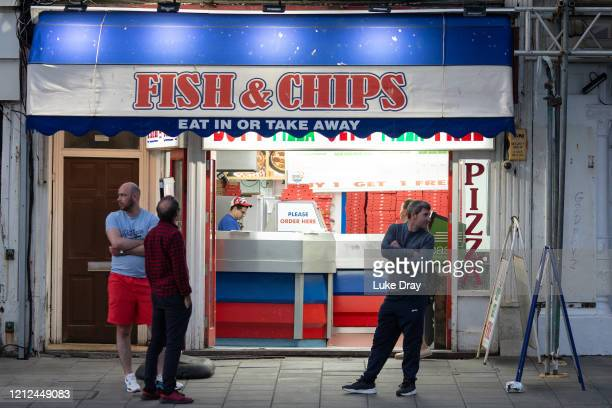 People wait outside a fish and chip shop on May 9, 2020 in Brighton, England. On Sunday February 2nd 2020 businessman Steve Walsh reported symptoms...