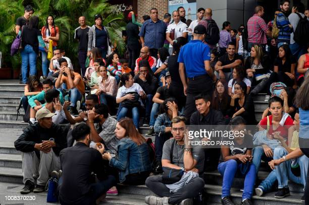 People wait outside a mall during a partial power cut in Caracas on July 31 2018 A power failure cut electricity to 80 percent of the Venezuelan...