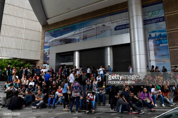 TOPSHOT People wait outside a mall during a partial power cut in Caracas on July 31 2018 A power failure cut electricity to 80 percent of the...
