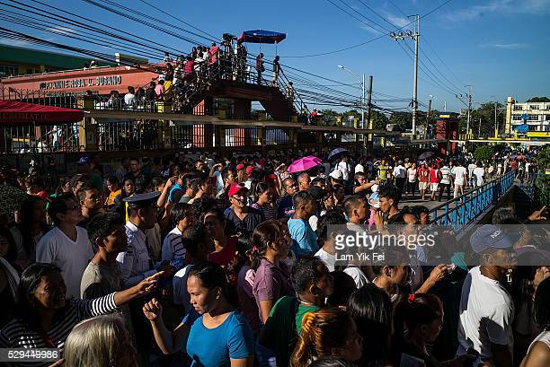 People wait outside a polling station on May 9 2016 in Manila Philippines Voters in the Philippines are set to elect Rodrigo Duterte a mayor of Davao...