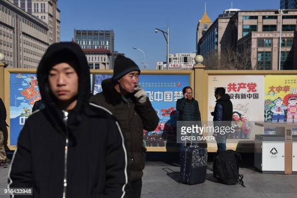 People wait outside a railway station in Beijing on February 10 as travellers depart the capital ahead of the Lunar New Year China is in the midst of...