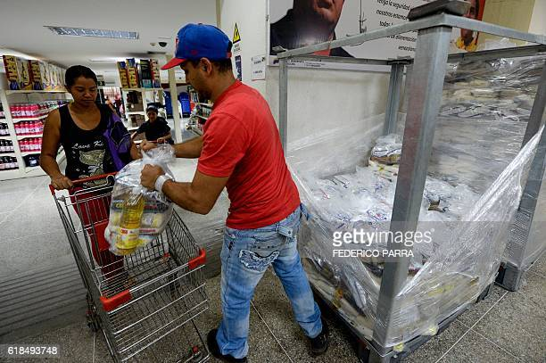 People wait outside a stateowned popular market after doing the shopping at the San Jose shantytown in Caracas on October 20 2016 Hit by the fall of...