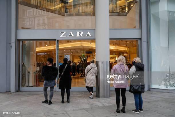 People wait outside a Zara store on Oxford Street on December 12, 2020 in London, England.