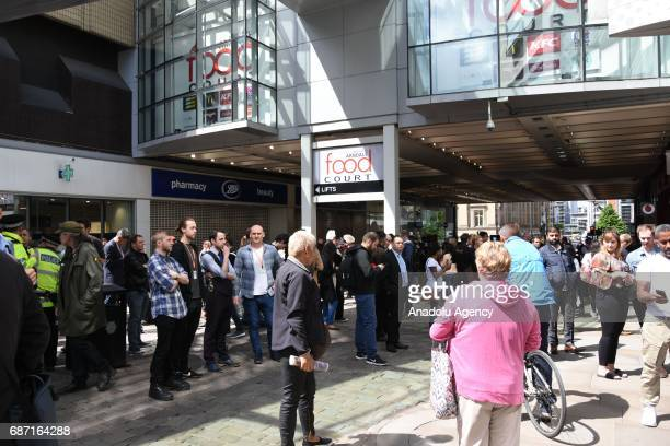 People wait outside Arndale shopping center which was evacuated by armed police in Manchester England on May 23 2017