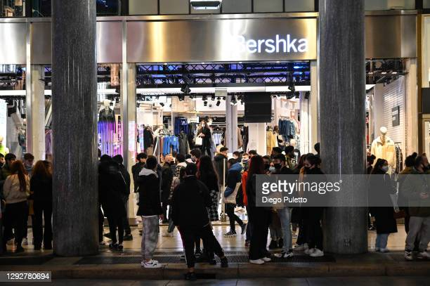 People wait outside at Bershka shop on December 23, 2020 in Turin, Italy. While decorations go up to celebrate the holiday season, Italy has banned...
