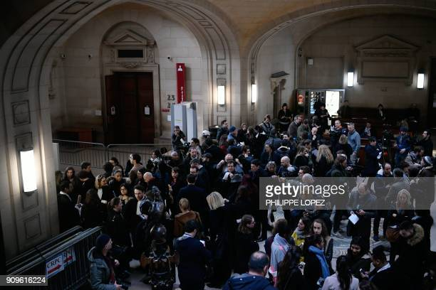 People wait outside the main courtroom ahead of the trial of Jawad Bendaoud charged with harbouring jihadists during the November 2015 terror attacks...