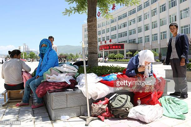 People wait outside the Minxian county hospital for treatment after an eathquake hit the area in Minxian county of Dingxi northwest China's Gansu...